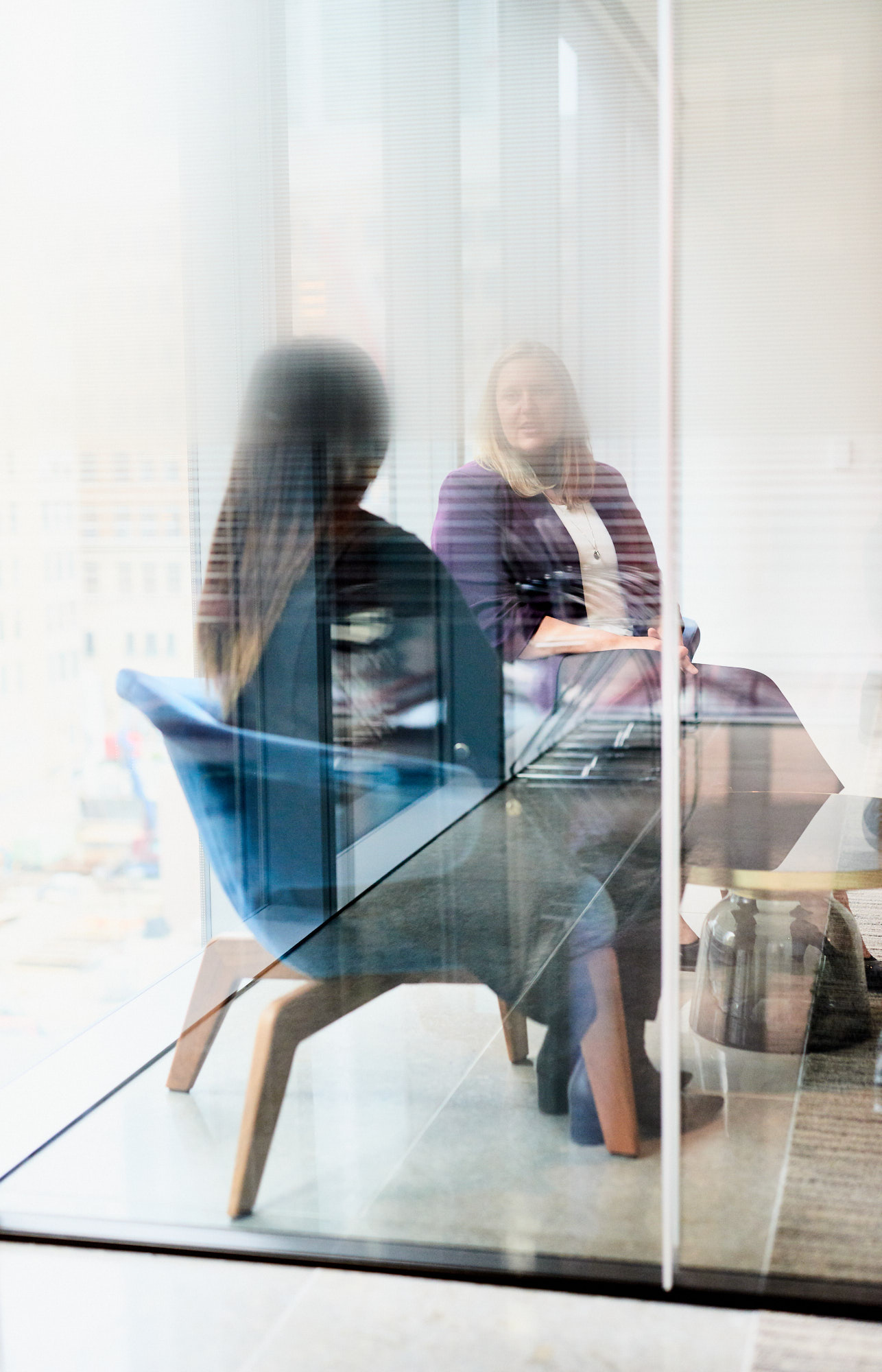 Two female business executives seen through glass wall chatting