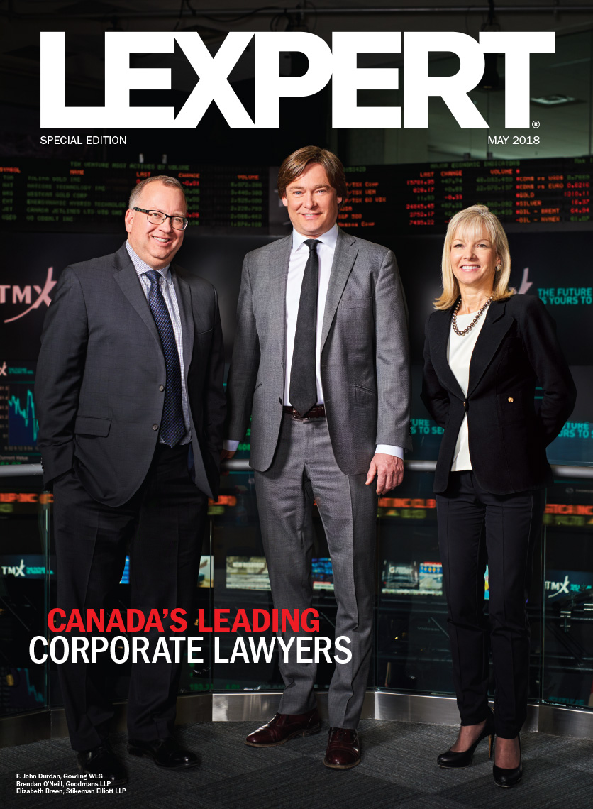 Full length three corporate executives in suits standing in the Toronto Stock Exchange